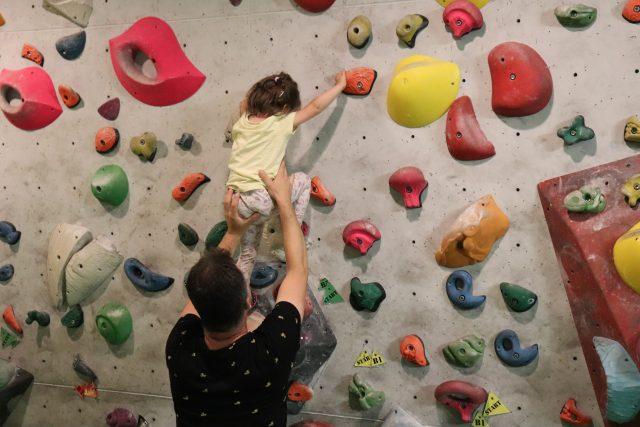 Tata pomaga trzyletniej córce stawiać pierwsze wspinaczkowe kroki na ściance
