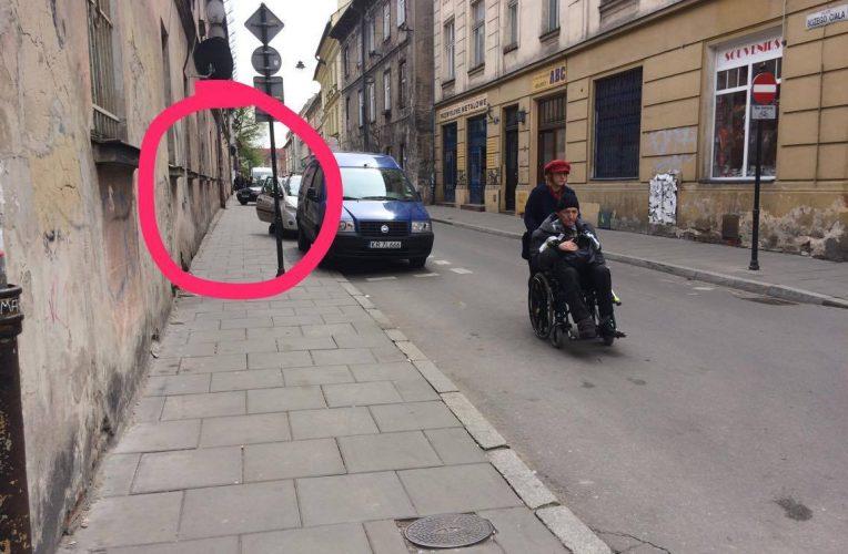 Na zdjęciu piesza z osobą na wózku poruszają się środkiem jezdni z powodu niemożliwości przemieszczania się chodnikiem z uwagi na źle zaparkowane samochody.